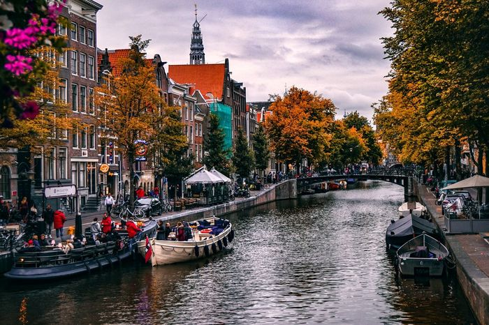 Beautiful canal of Amsterdam in Autumn. Amsterdam Amsterdam Canal Holland Netherlands Dutch Cities Dutch Iamsterdam Europe Europe Trip European  Autumn Autumn Leaves Autumn colors Water Architecture Tree Large Group Of People Building Exterior River Outdoors Built Structure Travel Destinations Sky Vacations Day Real People Nautical Vessel City People