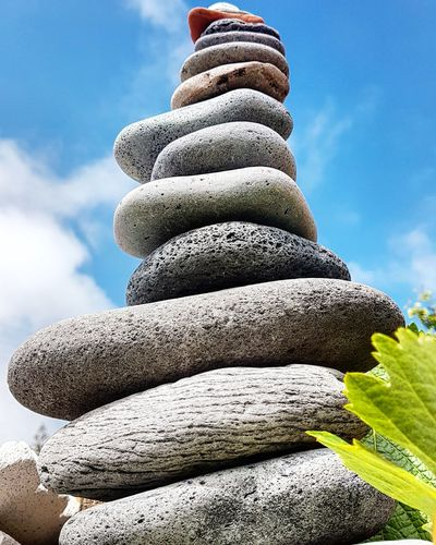 Low angle view of stone stack against sky