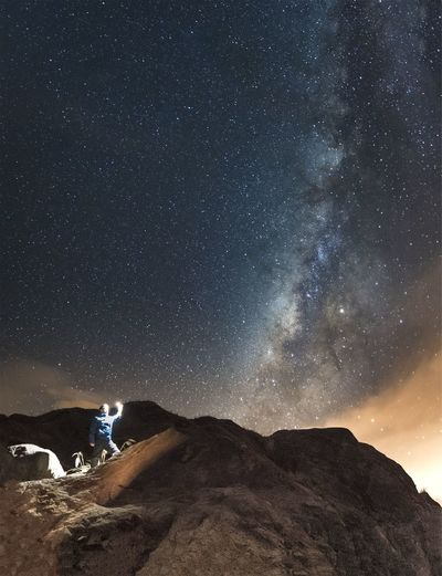 Man with illuminated lighting equipment on mountain against milky way