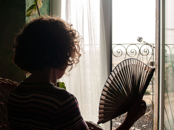 Woman Holding Hand Fan While Sitting On Seat At Home