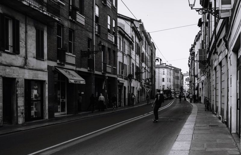 Full Length Of Man Skateboarding On Road Amidst Buildings In City