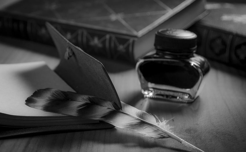 Close-up of ink and quill pen with diary on table
