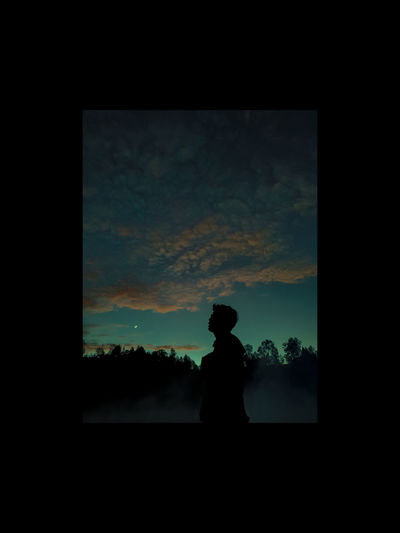 Silhouette man standing by window against sky during sunset