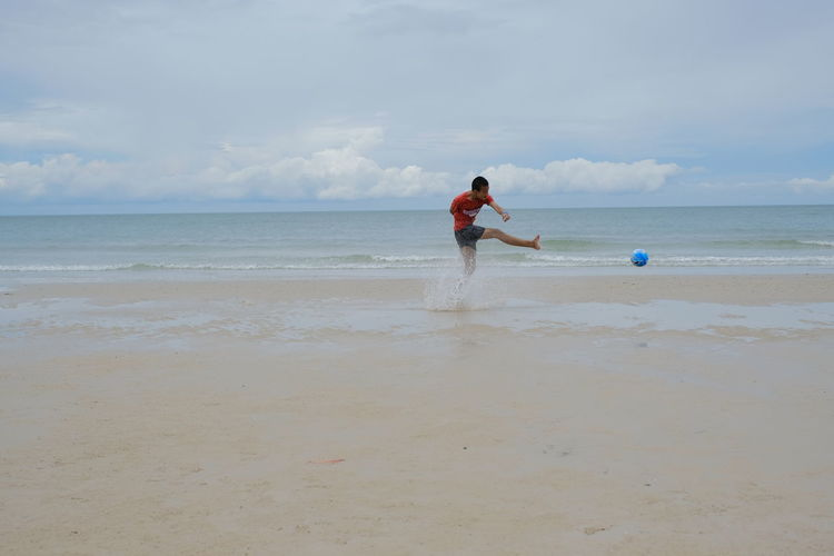 Man playing with ball on beach against sky