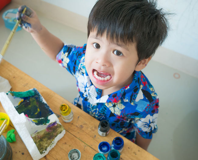 High angle view of cute boy painting on table at home