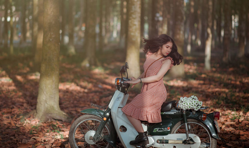 Young woman with bicycle on tree in forest