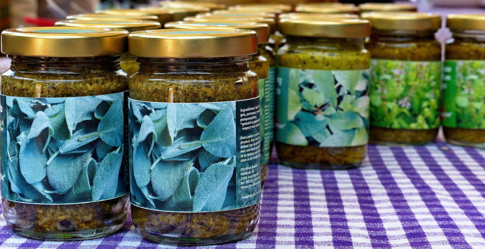 close-up glass jars with pesto sauce on a table Canned Food Close-up Food Glass - Material Glass Jars Glass Jars On The Table Healthy Food Herbs Jar Large Group Of Objects Lozenge Pattern Market Market Stall No People Pesto Pesto Sauce Table Cloth