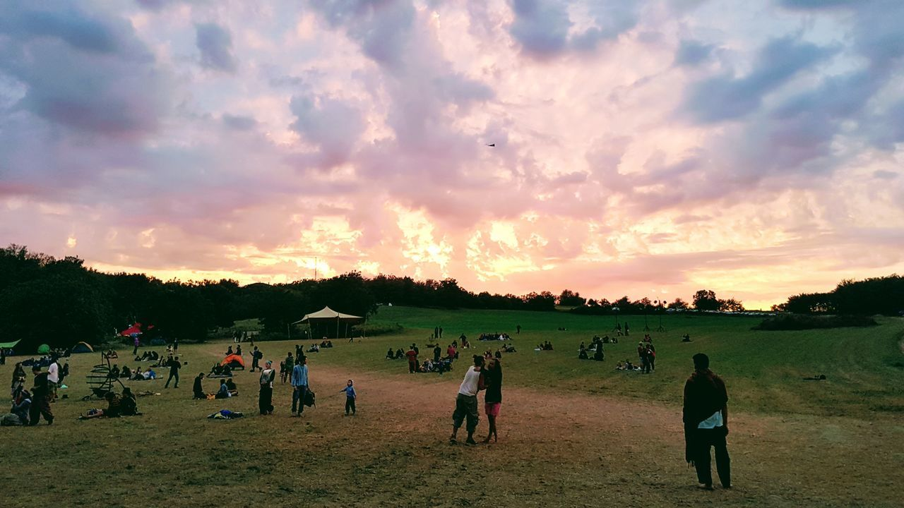 sunset, real people, sky, large group of people, men, cloud - sky, lifestyles, leisure activity, women, nature, beauty in nature, scenics, togetherness, outdoors, standing, landscape, tree, day, people, adult