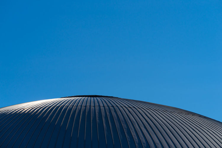 Low angle view roof toop of building against blue sky