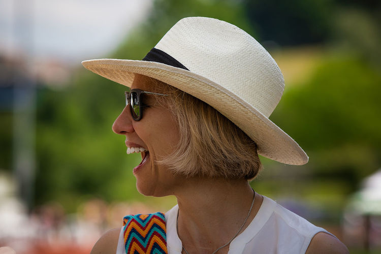 laughing Adult Beautiful Woman Close-up Clothing Day Fashion Focus On Foreground Glasses Hat Headshot Leisure Activity Lifestyles Looking Away Mouth Open One Person Outdoors Portrait Profile View Real People Sun Hat Sunglasses Women Young Adult