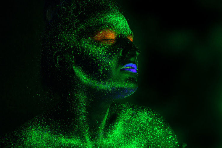 Woman with eyes closed in neon make-up