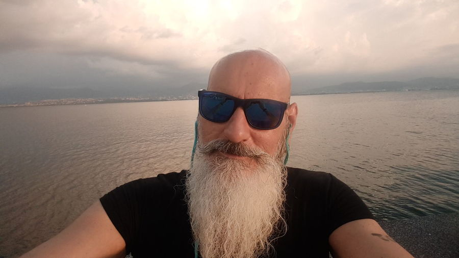 Close-Up Portrait Of Bearded Man Wearing Sunglasses Against Lake
