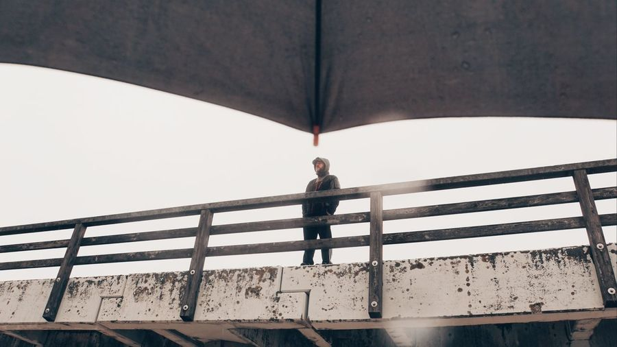 Low angle view of man standing by railing