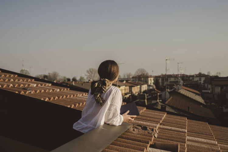 Woman standing on terrace against clear sky