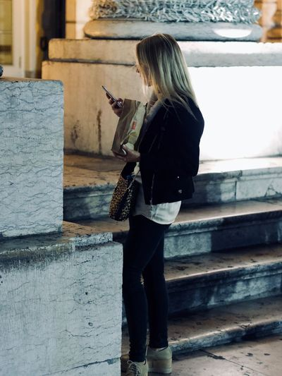 One Person Full Length Casual Clothing Real People Lifestyles Women Holding Adult Architecture Hair Leisure Activity Side View Blond Hair Built Structure Standing Long Hair Day Staircase Communication Hairstyle Outdoors