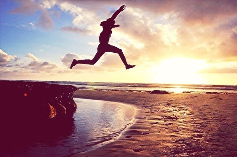 Silhouette of woman jumping on beach at sunset