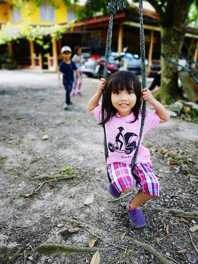 Portrait of smiling cute girl swinging outdoors