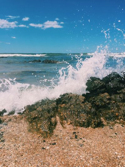 Scenic view of sea waves splashing on shore against sky