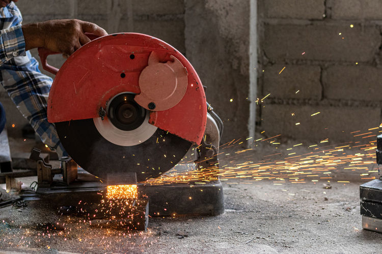Low section of man cutting metal