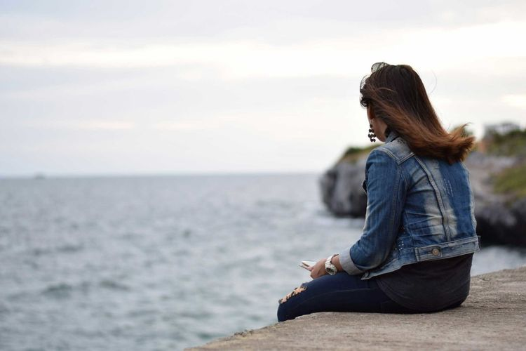 Side view of woman looking at sea while sitting on retaining wall against sky
