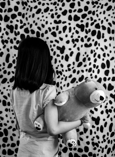 Rear view of girl holding teddy bear while standing by patterned wall