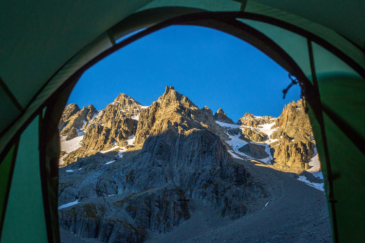 Snowcapped mountains seen through tent against clear sky