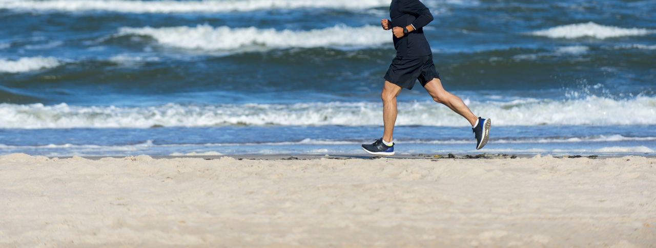 Low section of man running on shore at beach