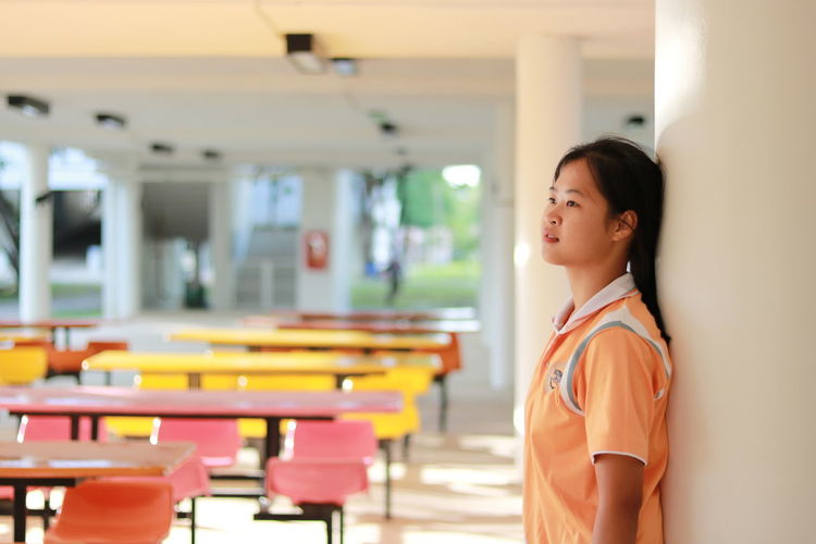 Side View Of Thoughtful Schoolgirl Standing By Column At School