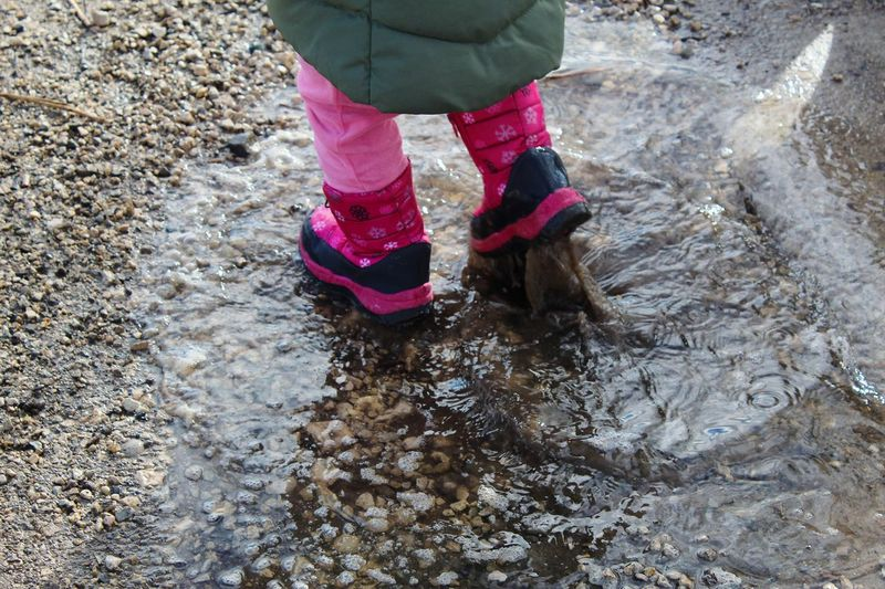 Low section of child walking in puddle