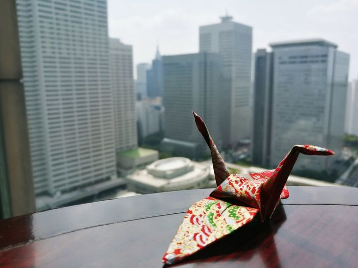 Close-up of origami on table against buildings in city