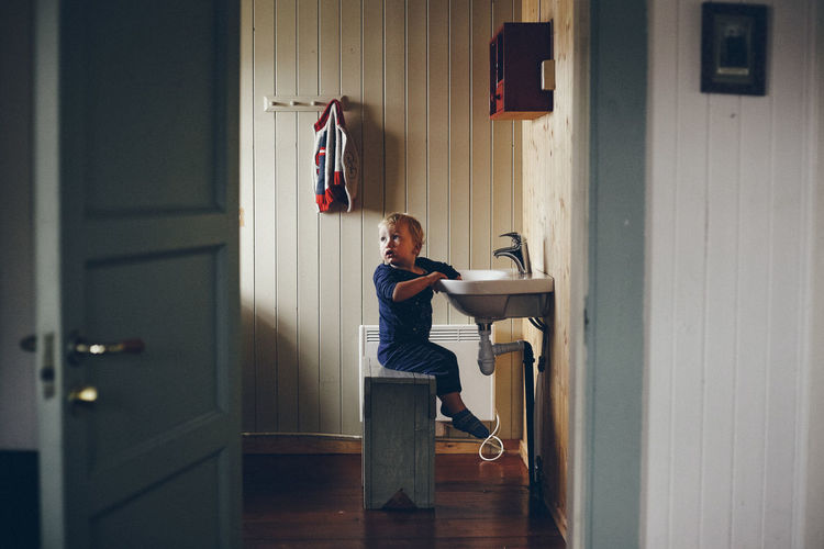 Side view of boy sitting by sink at home