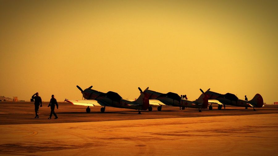 Silhouette Pilots Walking By Fighter Planes At Airbase During Sunset