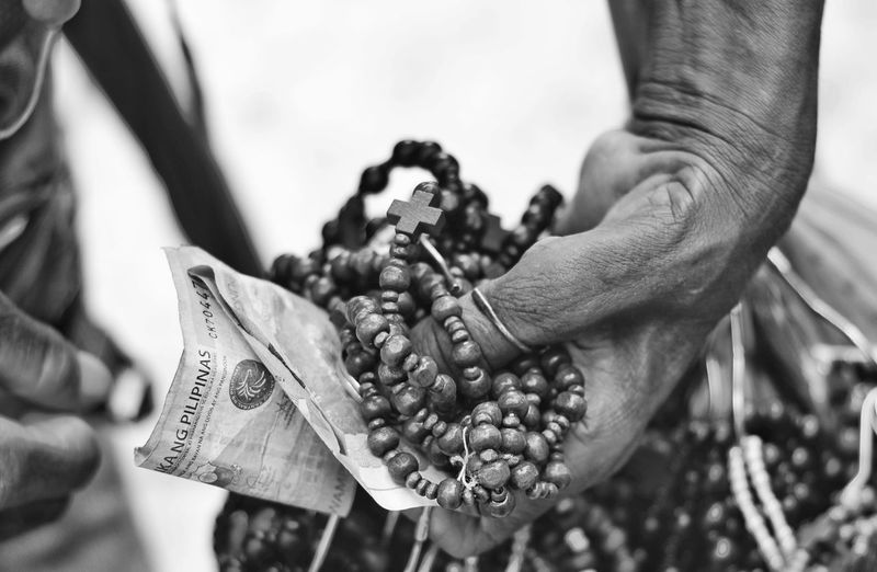 Cropped Hand Holding Rosary Beads And Money