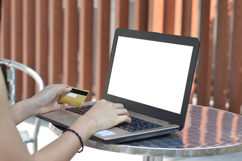 Online shopping Wireless Technology Technology Communication Connection Computer Internet Laptop One Person Holding Computer Network Portable Information Device Using Laptop Human Hand Mobile Phone Table Portability Indoors  Real People Smart Phone Adult Hand Blank
