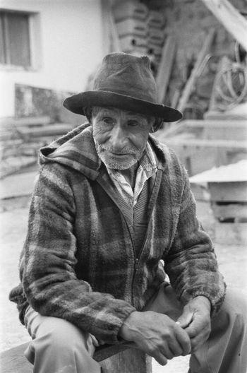Portrait of man wearing hat sitting in city