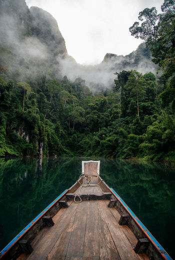 Rowboat in lake against trees and mountains