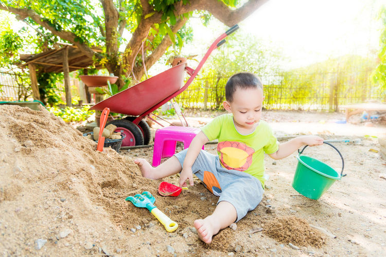 Boy playing with toy on sand outdoors