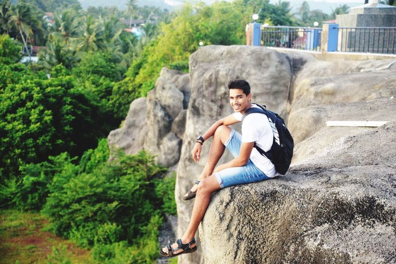Goan Fitness Indian Sitting Casual Clothing Outdoors One Person Shorts Full Length Tree Challenge Day Skill  People Horizontal Portrait Nature Young Adult Extreme Sports Rock Climbing Adult Person
