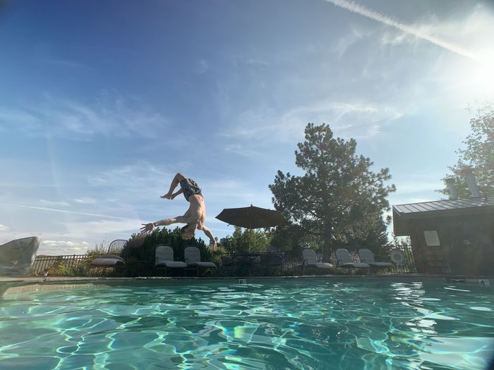 Man jumping in swimming pool against sky