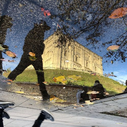 Reflection of people on street by building in city