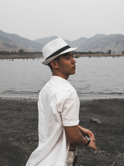 Side view of young man standing against lake