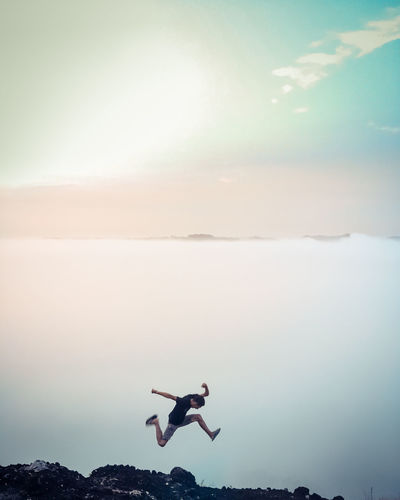 Low angle view of man paragliding against sky during sunset