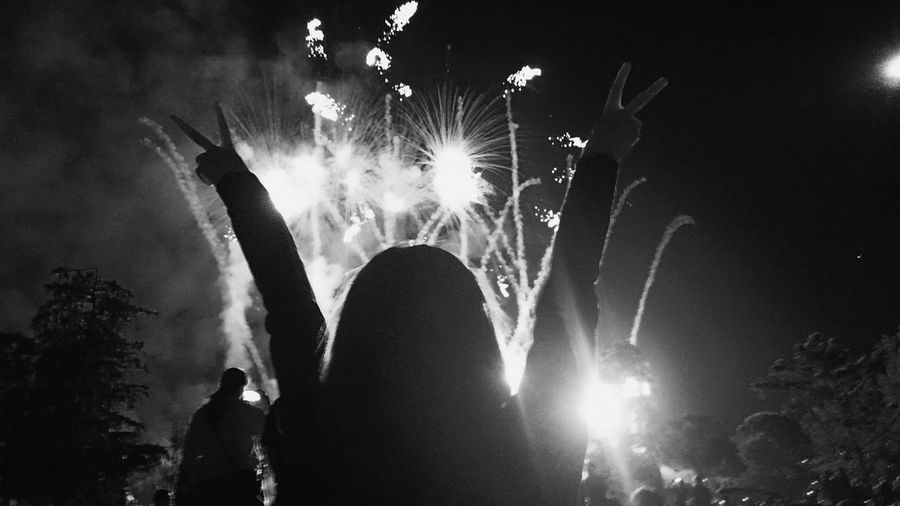 Rear View Of Woman With Peace Sign Against Firework Display At Night