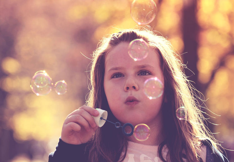 Close-Up Of Girl Blowing Bubbles Outdoors