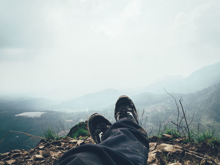 Low section of person on mountain against sky