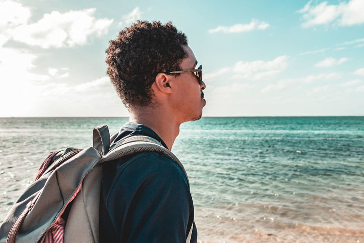 Side view of young man looking at sea against sky