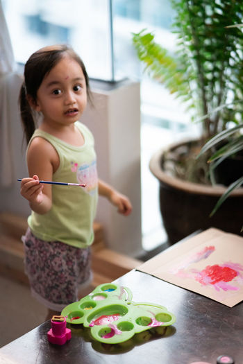 High angle portrait of girl painting on paper