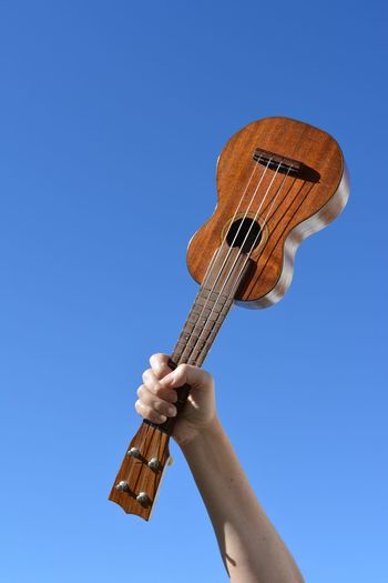 A ukulele in a woman's hand, held up in the air against blue sky with copy space. Musician Musical Instrument Positive Vibes Ukulele Time Ukulele Lover Ukelele Manila Ukelove Ukelife Uke Ukelele One Person Hand Human Body Part Human Hand Sky Real People Holding Clear Sky Unrecognizable Person Blue Low Angle View Music Day Musical Instrument Musical Equipment Arts Culture And Entertainment Body Part Playing Nature Finger
