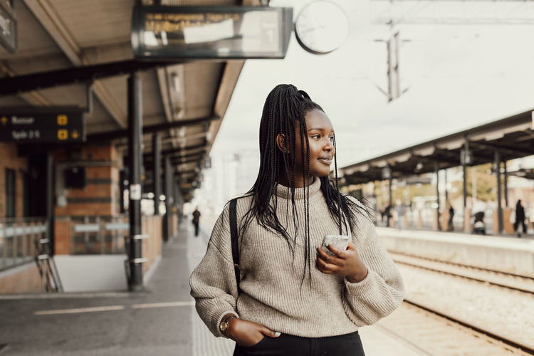 Portrait of young woman standing on railroad station