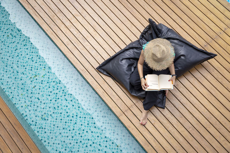High angle view of woman reading book while sitting by swimming pool